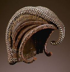 Africa | Wig (mukotte) from the Pende peoples, Democratic Republic of the Congo | Plant fibers, leather, brass tacks | This type of wig is based on a traditional coiffure styled with hair, clay, oil, copper nails, cowrie shells and, at times, beads. While both men and women wore the hairstyle, only men wore the wig as part of their daily attire. On special occasions it was embellished with parrot feathers.
