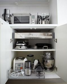 Store frequently used small appliances, such as a toaster and coffeemaker, on the counter. Store ones seldom needed in a lower cabinet. Install a drawer onto a deep lower shelf for appliances used occasionally, such as a rice cooker and blender.