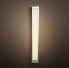 RH's Pierce Sconce:Our fluorescent-equipped fixture casts a soft light through its panels of sandblasted, ribbed white glass.