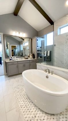Dual vanity bathroom with gray cabinets, tile rug inlay, modern bathtub, and huge shower with accent tile. Click to see more model home design ideas... THE DECORATING COACH #bathroomdesign