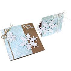 Kiinnitä korttipohjaan suikale kuviopaperia ja päällystä tulitikkuaski tarrakalvon ja kuviopaperin avulla. Kiinnitä kaksipuolinen tarrakalvo valkoiselle kartongille. Älä poista toista suojapaperia vielä. Leikkaa kartongista lumihiutaleita Big Shot -kuvioleikkurin ja stanssin avulla. Nyt voit poistaa lumihiutaleista tarrakalvon suojapaperin. Ripottele lumihiutaleiden päälle kimallejauhetta.