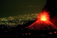 Perched above the lighted city of Catania, Italy, Mount Etna hurls a fountain of fire skyward as rivers of lava spill down its flanks.