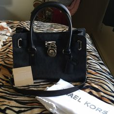 NWOT Attached Michael Kors Hamilton Logo Bag Black NWOT attached AUTHENTIC MK Hamilton small logo bag. Never worn/carried outside of my house, removed tags only. Black signature logo MK print. Silver hardware. Dustbag included. Absolutely no damage or wear. Photo 4 shows authenticity/serial code tab, MK tab, and hardware showing the MK name. ❤️EDIT: I've found the tag so that will be included.❤️ Price firm! Michael Kors Bags Shoulder Bags
