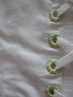 Cover the eyelets (grommets) on a corset or on a laced dress with embroidery thread in a contrasting color. Looks better, holds better. I think this would be a fabulous way to finish almost *any* grommet, especially on a bag or purse.