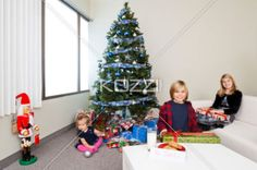 portrait of brother and sister with christmas gift box in a living room. - Portrait of brother and sister with Christmas gift box in a living room while a cute baby girl sitting beside Christmas gift present and Christmas tree. Model: Shania Chapman - Agent is Breann at MMG. breann@nymmg.com, Josh Chapman and Hannah Phillips