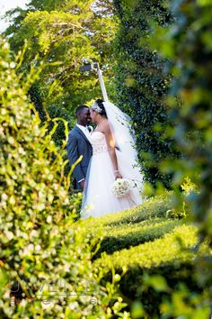 Candid photo of bride and groom shot between hedges.