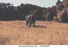 Cowgirl walking western horse through natural fall field, view from back.  Great agriculture or ranch and rodeo background image.
