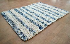 Upcycled denim blue jeans along with cotton and flannel fabric were used to make this striped rag rug. I made it using the old folk art way of rug making called twining. To do this, hand cut strips of fabric are twined or twisted onto a fabric warp which is strung onto a handmade wooden framed loom as seen in the photos above. By twining strips of fabric together, a rugged, durable, thickly textured rug is created! Measuring 35.5 x 27 inches and made out of thrifted and upcycled denim blue…