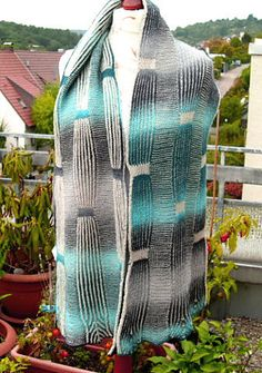 The stole combines stripes of 2-color brioche with stripes of 2-color garter stitch. This sets up some interesting color effects. By playing with the color sequence in the garter stitch, the brioche stripes end up being knitted in contrasting colors to the garter stitch bands. The double knitting stripes along the brioche bands add a third dimension to the color effects.