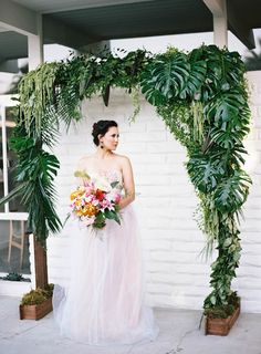 Ceremony- Another example of gorgeous greenery using tropical leaves and vines on an arch