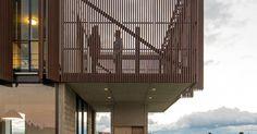 A pequena distância entre as ripas de madeira itaúba confere uma sutil transparência ao volume superior. Destaque para a sala de jantar com a varanda dotada de churrasqueira, no térreo.