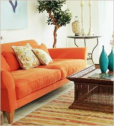 Don't be afraid of a bright color sofa like this orange sofa, for your mexican condo - beautiful when paired with natural tones and used as your focal piece.   Do you like?