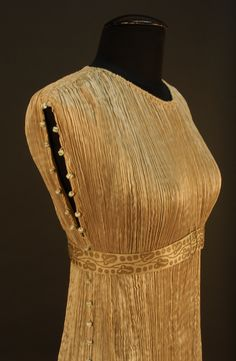 Side Detail Fortuny Delphos Gown with Original Box, c. 1920. Champagne pleated silk with separate gold stenciled empire waistband, armholes and side seams decorated to hem with white, blue and yellow Murano glass beads. Left shoulder closure.