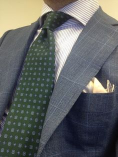 Grey windowpane suit, light greyish-blue striped shirt, green patterned tie, and cream patterned pocket square.