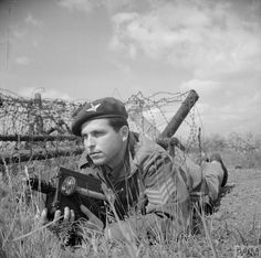 Sergeant Mike Lewis of the Army Film Unit posing with a De Vry, the camera most widely used by British combat cameramen. Mike Lewis transferred from the Parachute Brigade to the AFU, and filmed Arnhem and the liberation of Belsen.