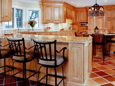 Saltillo+tiles+are+a+warm+pairing+with+this+kitchen's+honey+wood+cabinets.+Iron+barstools+and+a+chandelier+bring+in+a+hint+of+the+Mediterranean.