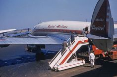 Capital Airlines Constellation loading passengers  Lockheed Constellation N86533 with a Northwest Airlines DC 4 in the background. Photo was taken in the mid-1950's at Rochester (NY) Monroe County Airport [?] Photo by George Lane