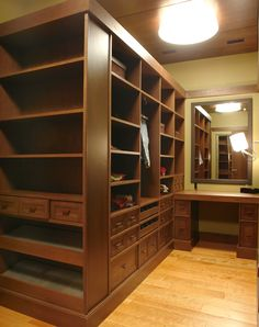Custom walk in closet with mirror and wood flooring