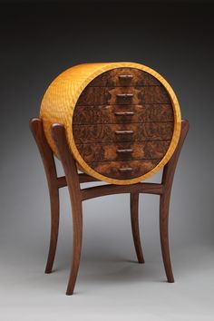 "Blase Mathern, Jr.'s ""Satin Cirque"" custom jewelry box__ Dimensions48"" (H) X 31"" (W) X 21"" (D)__crafted out of African Satinwood scrupulously affixed to its core. The veneers are cross-banded to create a two-ply skin, which strengthens the face veneer before application. Each drawer is composed of solid Walnut. A bold specimen of two-piece book matched Walnut Burl veneer and leather lined. __co$t: 15k"