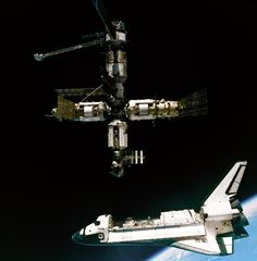 A view of the Space Shuttle Atlantis departing the Mir Russian Space Station. This image was taken during the STS-71 mission by cosmonauts aboard their Soyuz TM transport vehicle. The scene is backdropped by the Earth's limb. (NASA).
