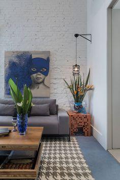 Decoração rústica e sofisticada de living jovem, Casa Cor, parede de tijolinhos, vaso azul, plantas na decoração, sofá cinza, mesa de centro de madeira e quadro, arte.