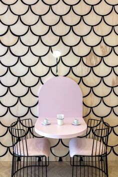 This modern patisserie features a graphic wood accent wall that features the u-shape, also known as a scalloped or fish scale pattern. The wall design wraps from the wall up onto the ceiling and over to the service area. #ModernCafe #Patisserie #InteriorDesign
