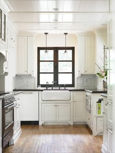 white cabinets with black counters, appliances and accents
