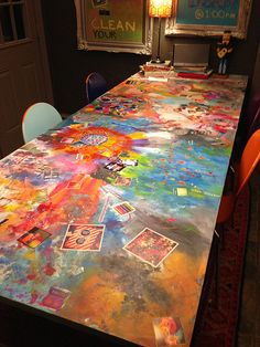 Kitchen table art project.  What to do with an old, crappy Ikea table?  Paint it!  This is an interactive art piece.  Mixed media, paint, photographs... all on the dining room table.  Ideas for your art house.