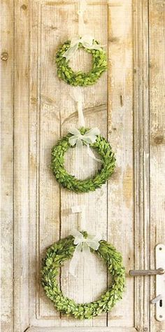 Simple greenery wreaths with white, sheer bows can look so beautiful,