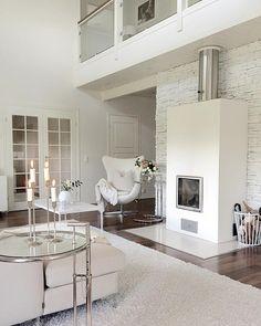Kodikas ja elegantti valkoinen sisustus, joka hehkuu samalla kodikkutta ja ylellistä tunnelmaa. Upea nojatuoli takan vieressä kruunaa tyylin.