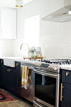 white backsplash, black cabinets with brass hardware, brass faucet, oriental rug