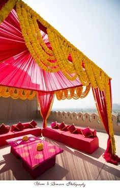 Pretty swirls of marigold - destination diaries! Pink mehendi canopy paired with yellow gainda #IndianWedding #decor #ideas | photo by : Bhooma and Simran photography | curated by Witty Vows - The ultimate guide for the Indian Bride | www.wittyvows.com