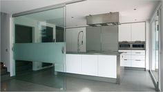 Inox keuken met witte keukenkasten. Een glazen schuifdeur van Anywaydoors kan de open keuken makkelijk afscheiden indien er bezoek komt.