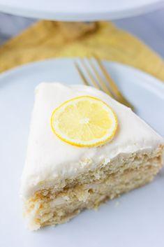 slice of vegan lemon cake on a plate with gold fork