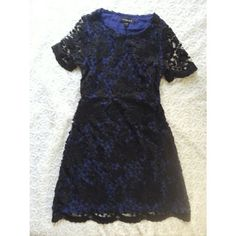 {boutique} black & blue lace dress Look so elegant in this knee length black and blue lace dress from evette & k. Sheer black lace sleeves. Side zip. Has pockets! Brand new with tags!  A great dress for a work party or for work with a croppes black blazer and blacl leather oxfords.  Size xs evette and k Dresses