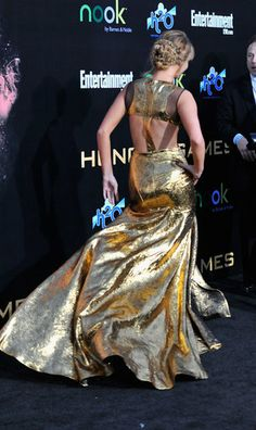 Jennifer Lawrence Lights Up The Hunger Games Premiere — See Every Jaw-Dropping Angle: On her way to the theater — we love the way Jennifer's train got caught in the breeze.  : With each step, the gold lamé gown caught the light perfectly.