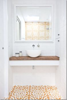 Love this small bathroom design with floating white counter topped with unfinished reclaimed wood counter top, small white basin sink, wall-mounted silver sink faucet, and gorgeous dark yellow, tan and white printed Spanish-inspired tiles on the floor and New York Loft, Bad Inspiration, Bathroom Inspiration, Bathroom Ideas, Bathroom Styling, Bathroom Makeovers, Remodel Bathroom, Bathroom Inspo, Bathroom Designs