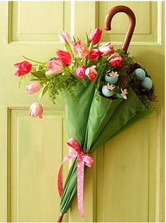 An umbrella filled with spring flowers and a bird's nest with eggs