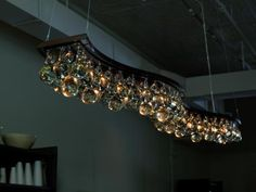 Arctic Pear Chandelier - double wave 200cm. Featuring a patinated bronze of nickel frame with solid clear glass drops. 1 tier with additional drops on central channel.    OCHRE lighting design