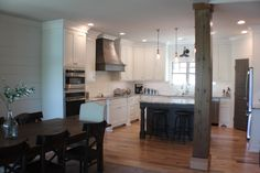 Lake Home with reclaimed wood architectural details, custom kitchen, built-ins, barn door, teak dining table, wood plank walls,