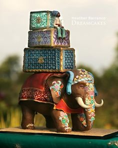 Gorgeous Indian themed wedding cake featuring and elephant carrying ornate boxes in a palette of blue, gold, green, red, pink, and yellow. Truly unique and creative.