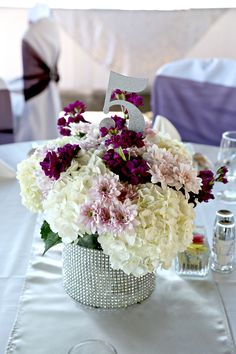 Flowers by Sisters Floral Design www.sistersflowers.net  Image by Woven Bone Photography.  Lavender mums, dark purple stock, white hydrangea, bling band, flower centerpieces