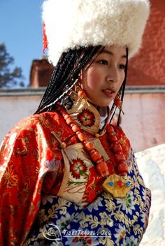 """""""Most Tibetan women plait their hair into numerous small pigtails, and their headwear is usually a natural gemstone, such as amber, coral, agate, etc. In styles of wearing, some fix the adornment directly in the pigtails, some fix all kinds of headwear they have chosen onto a piece of cloth which is close to the hair color, and then connect it to their pigtails: being both beautiful and convenient."""" -tibettravel.org"""