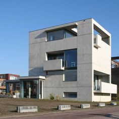 This cast-concrete house in Almelo, in the Netherlands by Dutch practice Van der Jeugd Architecten has balconies that appear as extrusions of the walls.