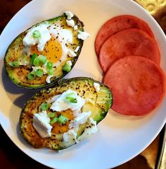 Healthy breakfast idea with avocado, 2 eggs, green onions, goat cheese, and a little salt and pepper baked for a few minutes so the egg is still runny. Served with a side of ham slices! It is possible to eat healthy and enjoy every minute of it! My diet is kind of a keto/paleo situation, and I always love what I make for breakfast, lunch, and dinner. Starting the day with something like this will leave you feeling great all day!