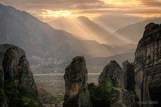 Sunbeams break through the clouds behind the sandstone pillars of Meteora, Greece.