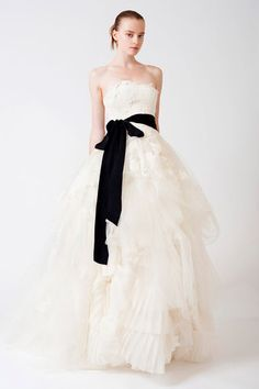 Vera Wang strapless tulle ball gown with floating chantilly & alencon lace appliqued bodice. Softly tucked skirt with swirling pleated organza insert and grosgrain sash at natural waist. Dress has bee