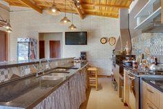 """O espaço gourmet desta residência em Araucária (PR), projetado pela arquiteta Juliana Lahóz, apresenta piso em porcelanato e forro de madeira, além dos pendentes em estilo """"country"""". O balcão da churrasqueira é revestido com porcelanato que imita os ladrilhos hidráulicos. O mobiliário da cozinha é feito sob medida em MDF"""