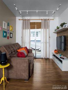 Sala pequena com acessórios coloridos, uma parede em tom diferente, madeira e branco formam belo contraste.