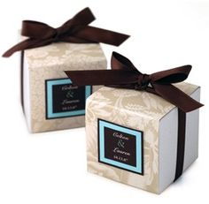 """Tropical Brown Elegance Favor Box Box Size: 2"""" x 2"""" x 2"""" Let your guests indulge themselves in your good taste with our Tropical Brown Elegance Favor Boxes. These custom favor boxes are designed with an Anna Griffin floral linen print and are accented with a soft mocha brown ribbon. The inside of the patterned box holds a handful of tasty treats. Choose from chocolate covered coffee beans, Jordan almonds and other delicious candies. Add a custom tag to give your favor a truly personal touch…"""